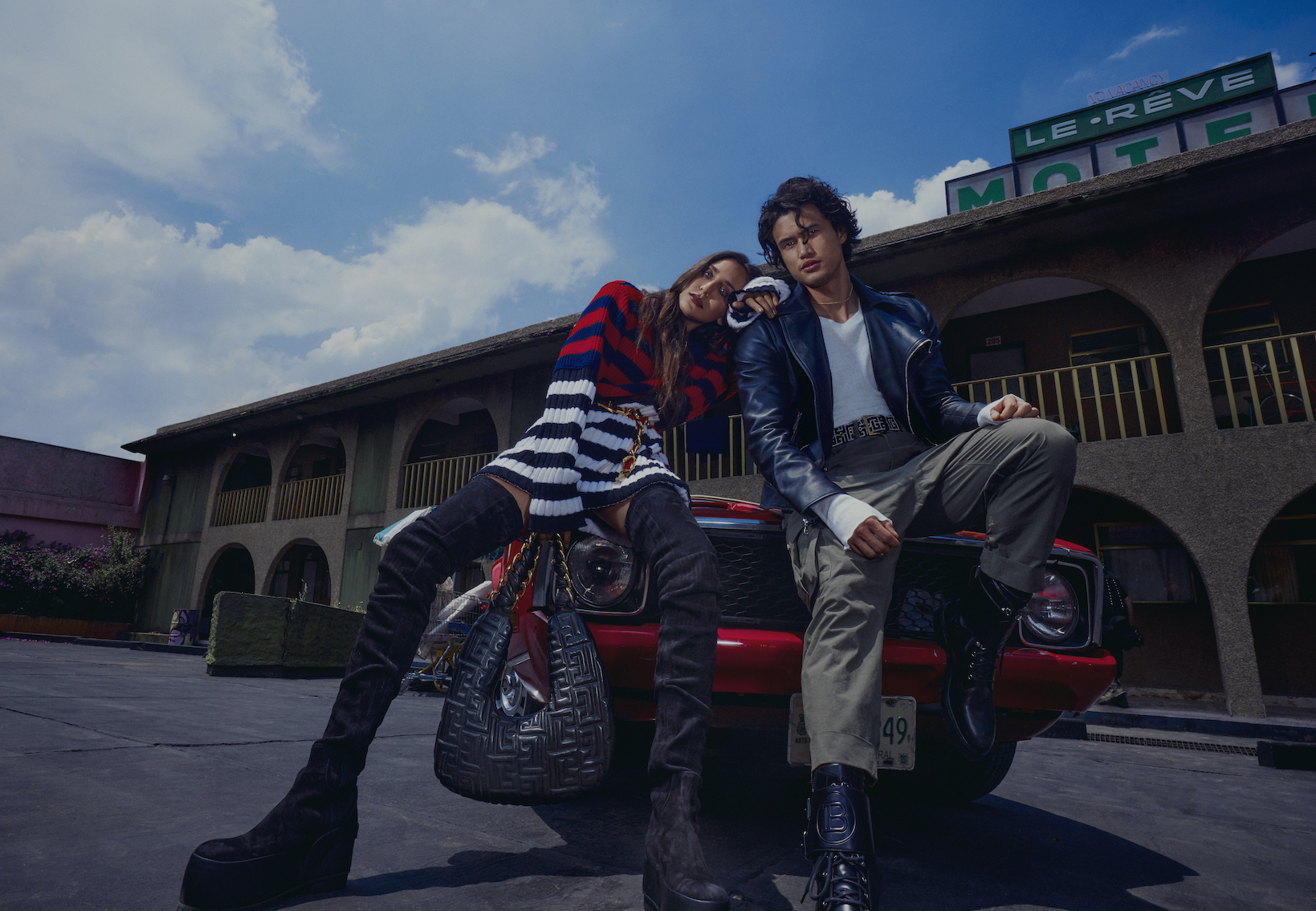 male and female model sitting on a car